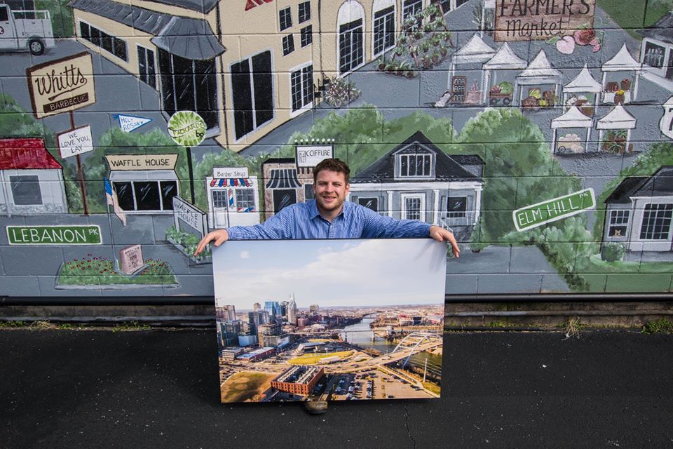 Derek holding one of him images printed on a large canvas